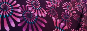 Andromeda Meadow 02 fabric. Vibrant pinky purple spirals with turquoise detail on dark purple background.