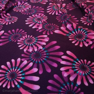 Psychedelic pink spirals print on fabric.
